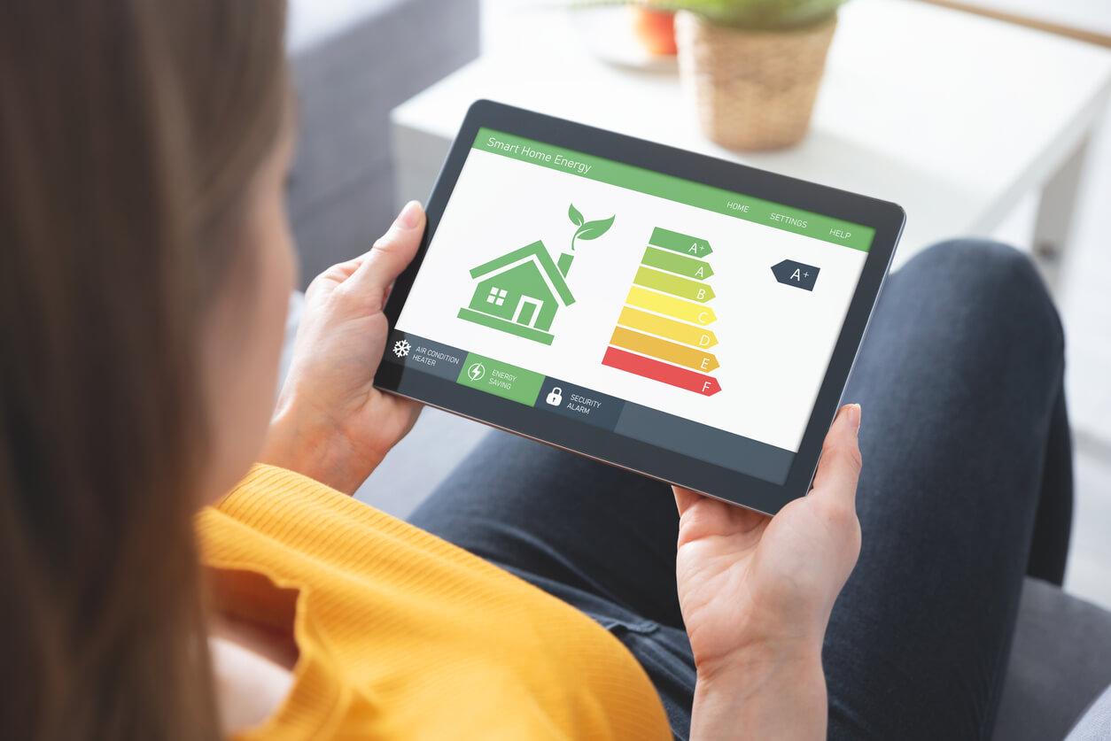 Kobieta ogląda natablecie energooszczędny dom