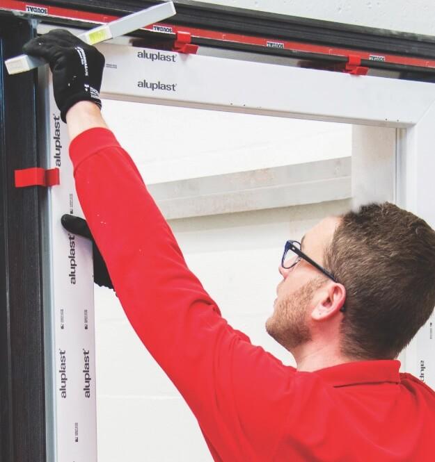 Montażysta instaluje okno nakonsoli